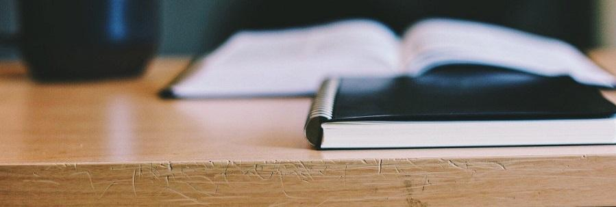 Photo of a book, journal and mug on a desk